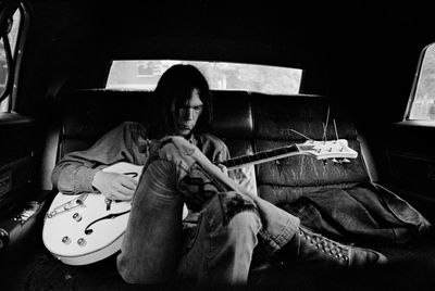 Neil-young-guitar-back-of-car-band-in-car
